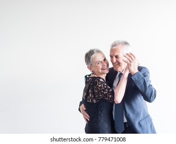 Mid length view of elegantly dressed older man and woman dancing against neutral background (selective focus)