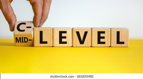From mid level to C level. Hand turns a cube and changes the words 'mid level' to 'C level'. Beautiful yellow table, white background, copy space. Business concept.