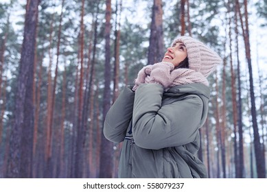 Mid outdoors shot of woman holding scarf on a wintry day. Woman in a padded jacket with knitted scarf and mittens. Breathtaking landscape with snow-capped branches of tree