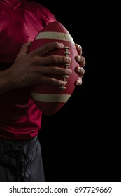 Mid section of American football player holding a football with both his hands