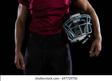 Mid section of American football player holding a head gear