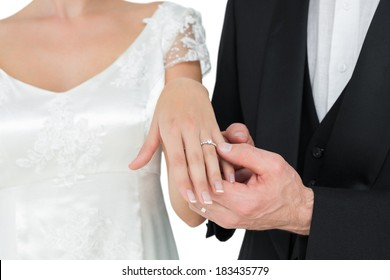 Mid section of bride and groom showing wedding ring against white background