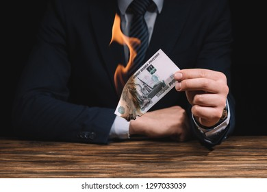 mid section of businessman burning russian rubles banknote above wooden table