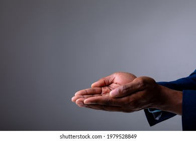 Mid section of businessman with cupped hands against grey background. business, professionalism and technology concept