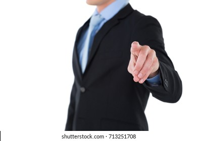 Mid section of businessman gesturing on invisible interface while standing against white background