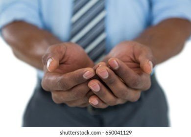 Mid section of businessman with hands cupped against white background