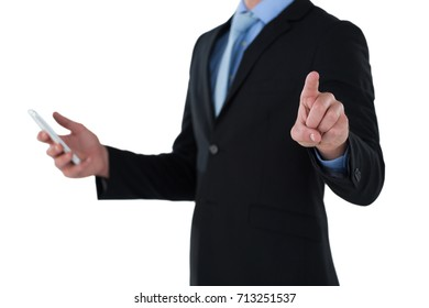 Mid section of businessman holding mobile phone while using interface screen against white background