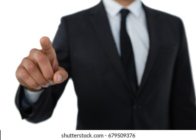 Mid section of businessman with pointing gesture standing against white background
