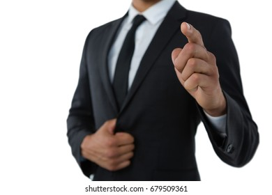 Mid section of businessman pointing while standing against white background