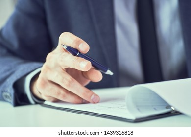 Mid section of businessman reading rental contract before making a deal. Corporate man with pen in hand working in modern office, signing business document on desk. close up.