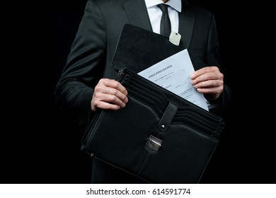 Mid section of businessman in suit  holding briefcase with papers  isolated on black