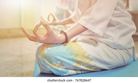Mid section of calm young woman meditating against motivational, success and determination concept.