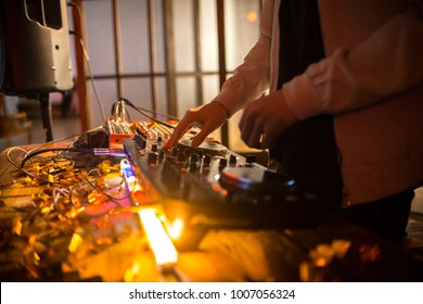 Mid section close up of young DJ playing music in trendy club, focus on hands over DG mixer with lit up lights, copy space