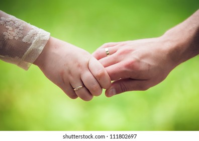 Mid section closeup image of a young couple holding hands, outdoors