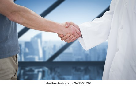 Mid section of a doctor and patient shaking hands against room with large window looking on city