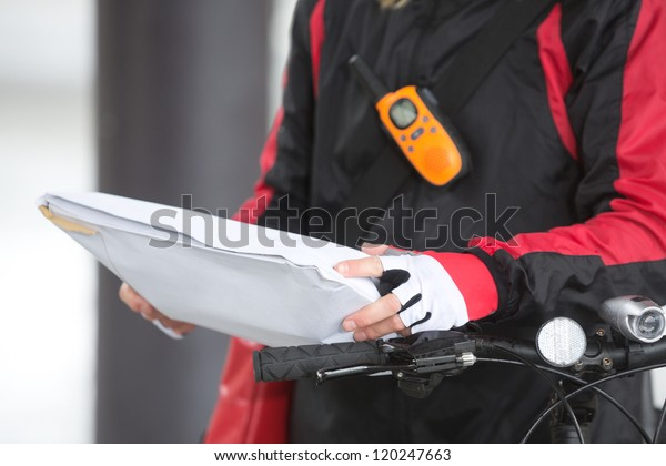 Mid section of female cyclist holding courier package