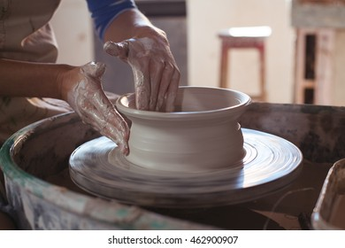 Mid section of female potter making pot in pottery workshop