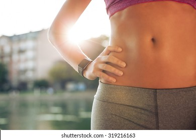 Mid section of fit woman's torso with her hands on hips. Female runner wearing smartwatch device with sun flare, outdoors.