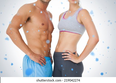 Mid section of a fit young couple against snow falling