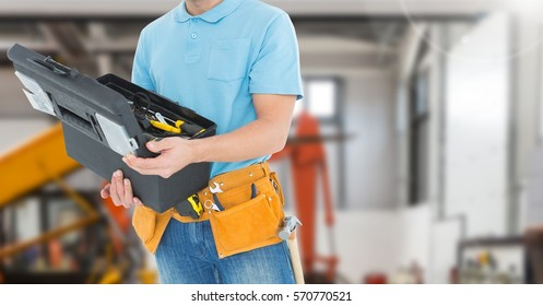 Mid section of handyman holding toolbox in workshop