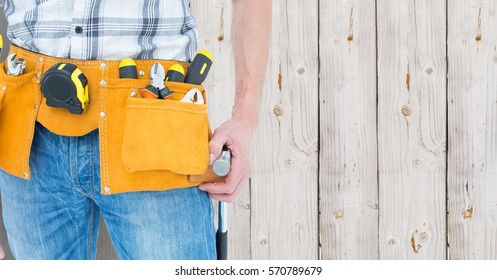 Mid section of handyman with tool belt around his waist against wooden background