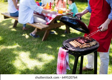 Mid section of man barbequing in the park