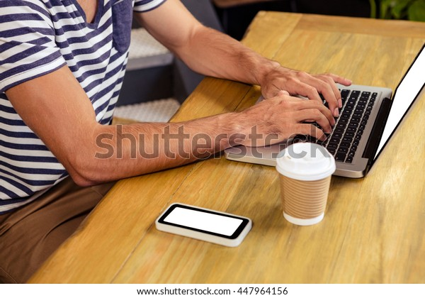 Mid section of man using laptop in cafeteria