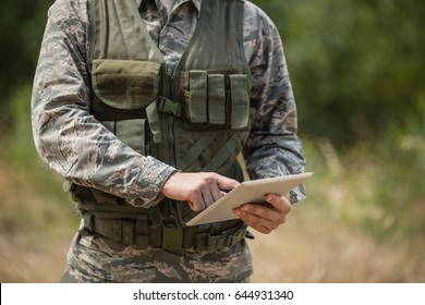 Mid section of military soldier using digital tablet in boot camp