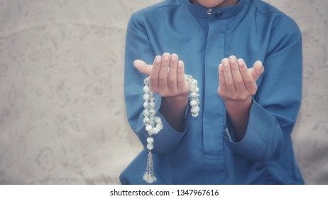 mid section of a Muslim boy with hand praying during holy month of Ramadan