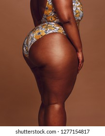 Mid section of overweight woman body. Plus size dark skinned female with big  hips wearing a swimsuit standing against brown background.