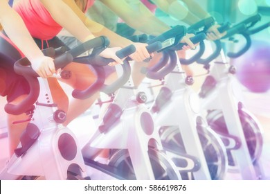 Mid section of people working out at spinning class against abstract background