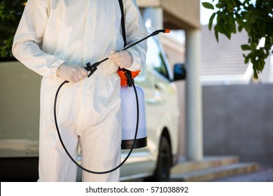 Mid section of pest control man standing next to a van on a street