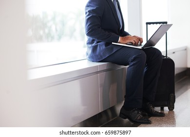 Mid section portrait of unrecognizable businessman using laptop in airport while waiting for plane with big suitcase