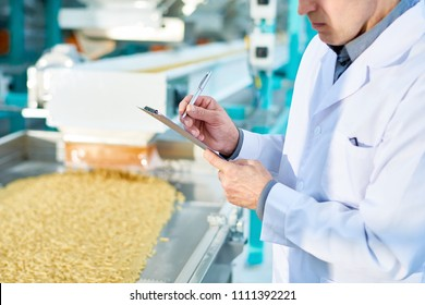 Mid section portrait  of  unrecognizable factory worker doing  production quality inspection in food industry holding clipboard and standing by conveyor belt, copy space