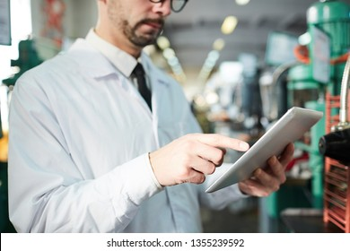 Mid section portrait of unrecognizable factory worker using digital tablet while operating modern machines in workshop, copy space