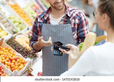 Mid section portrait of young woman paying via smartphone while grocery shopping in supermarket, copy space