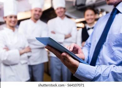 Mid section of restaurant manager using digital tablet in commercial kitchen