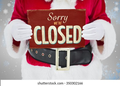 Mid section of santa claus holding page against vintage closed sign