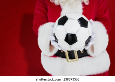 Mid section of santa holding football against red snowflake background