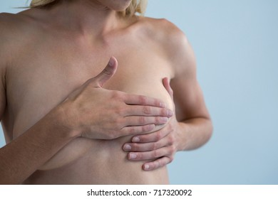 Mid section of shirtless woman checking for lumps while touching breast against gray background