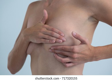 Mid section of Shirtless woman checking for lumps while examining breast cancer against gray background