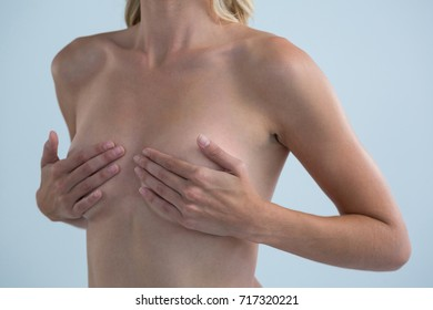 Mid section of shirtless woman with hands on breast standing against gray background