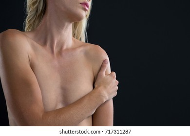Mid section of shirtless woman while standing against black background