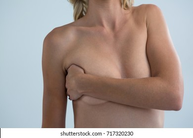 Mid section of shirtless young woman with hand on breast standing against gray background