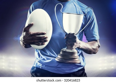 Mid section of sportsman holding trophy and rugby ball against spotlights