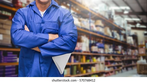Mid section of supervisor standing with arms crossed in warehouse