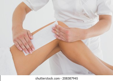 Mid section of therapist waxing woman's leg at spa center