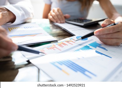Mid- Section Of Two Businesspeople Analyzing Graph Over Office Desk
