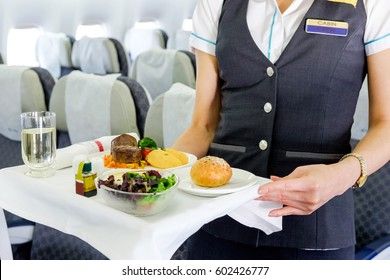 Mid section view of an air hostess carrying a tray of food