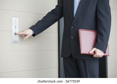 Mid section view of a businessman pressing button for elevator in an office building